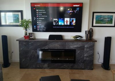 Flat screen tv mounted on wall with Goldenear speaker towers